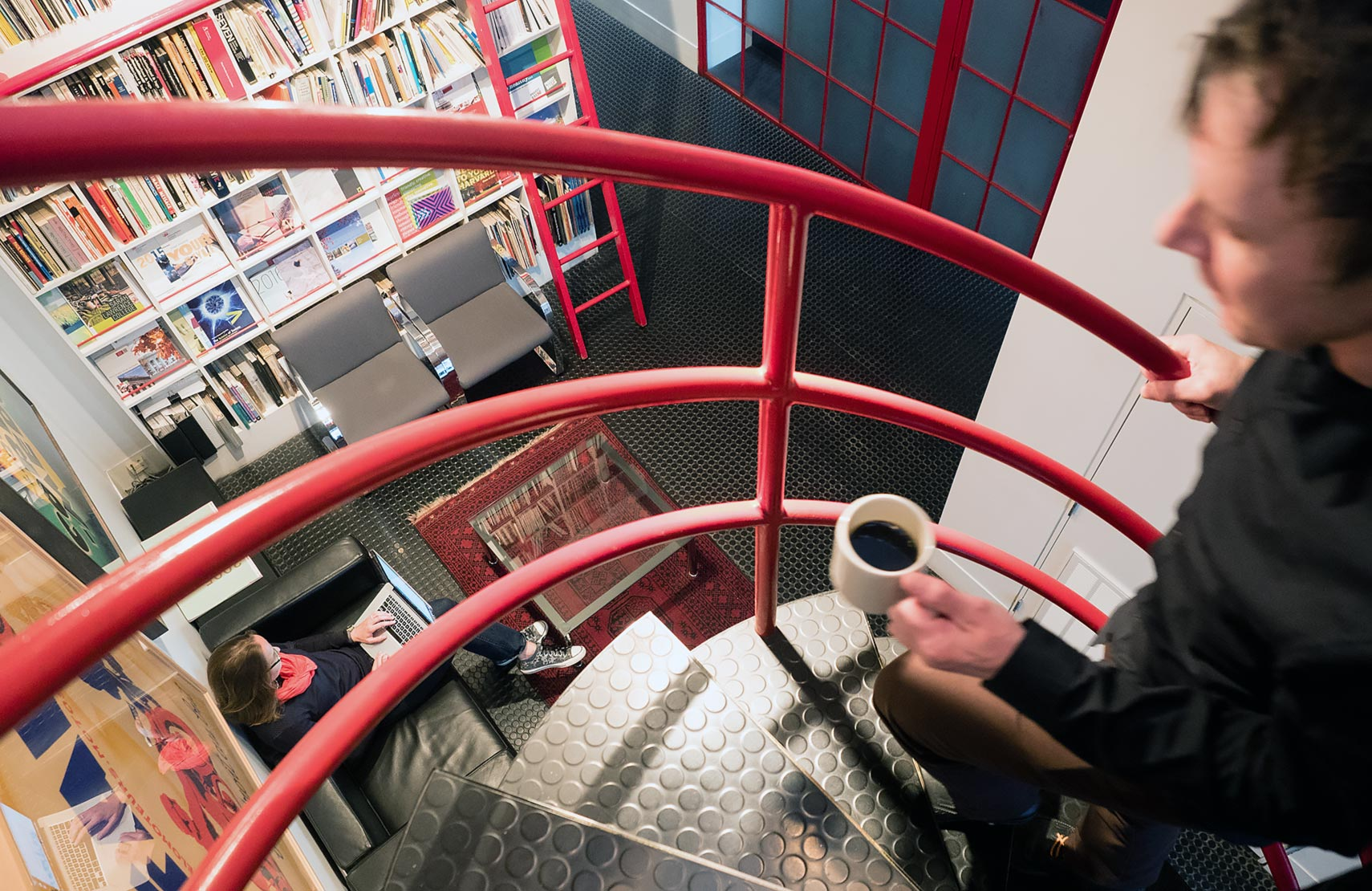 View from the top of the spiral staircase in Sametz Blackstone Associates; Paul Kruczynski a walking up the stairs and Ange Romanska sitting on the couch down below
