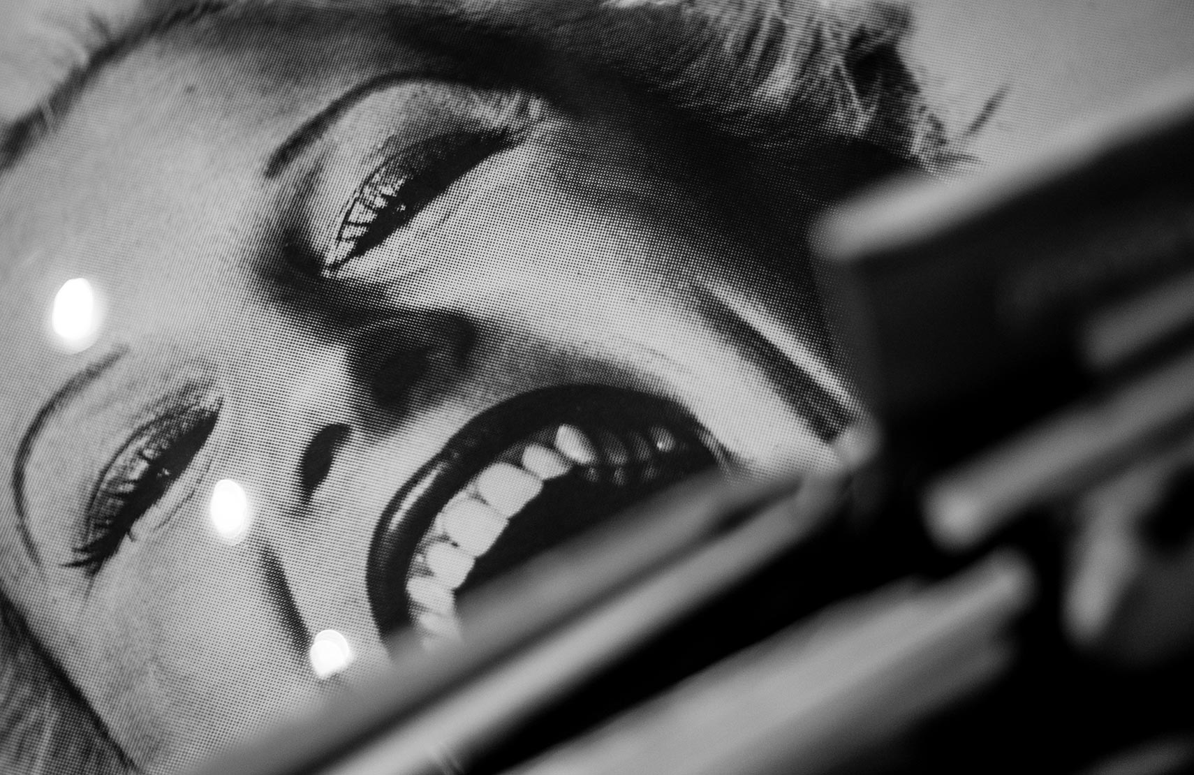 A poster of woman smiling up-close in black and white