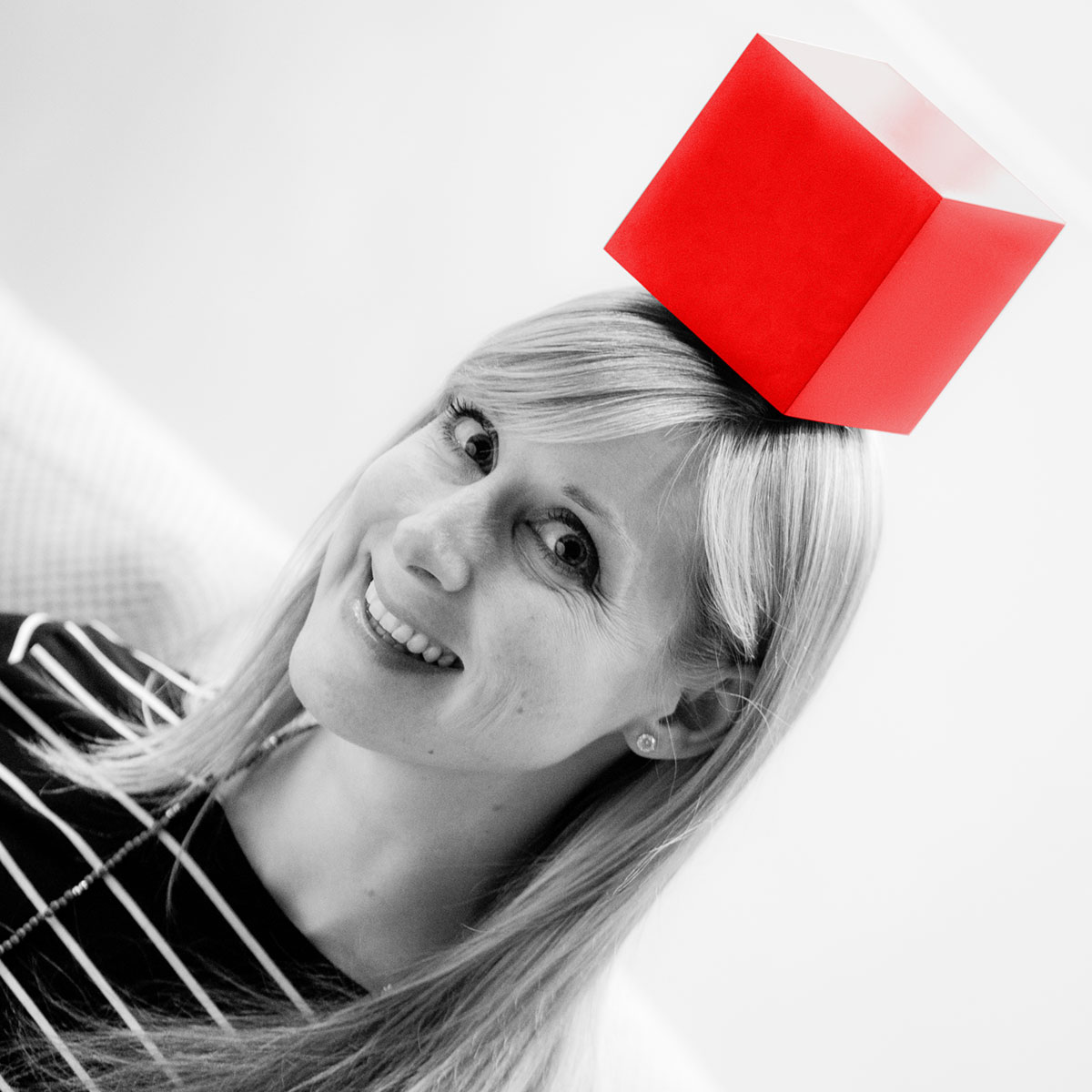 Caity Mclaughlin Lischick in black and white, with a bright red cube on her head