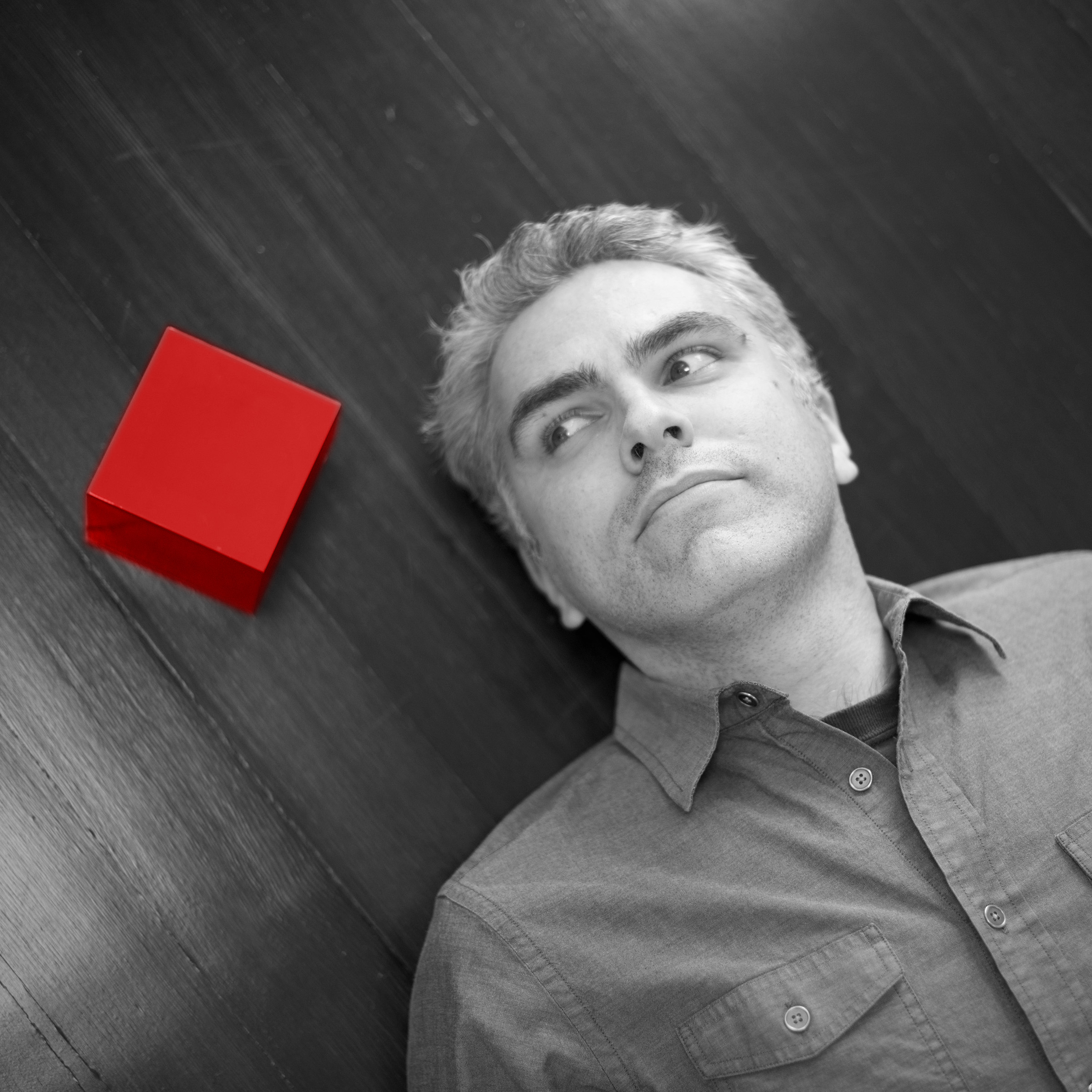 Alex Budnitz in black and white, laying on the ground, with a bright red cube on his head