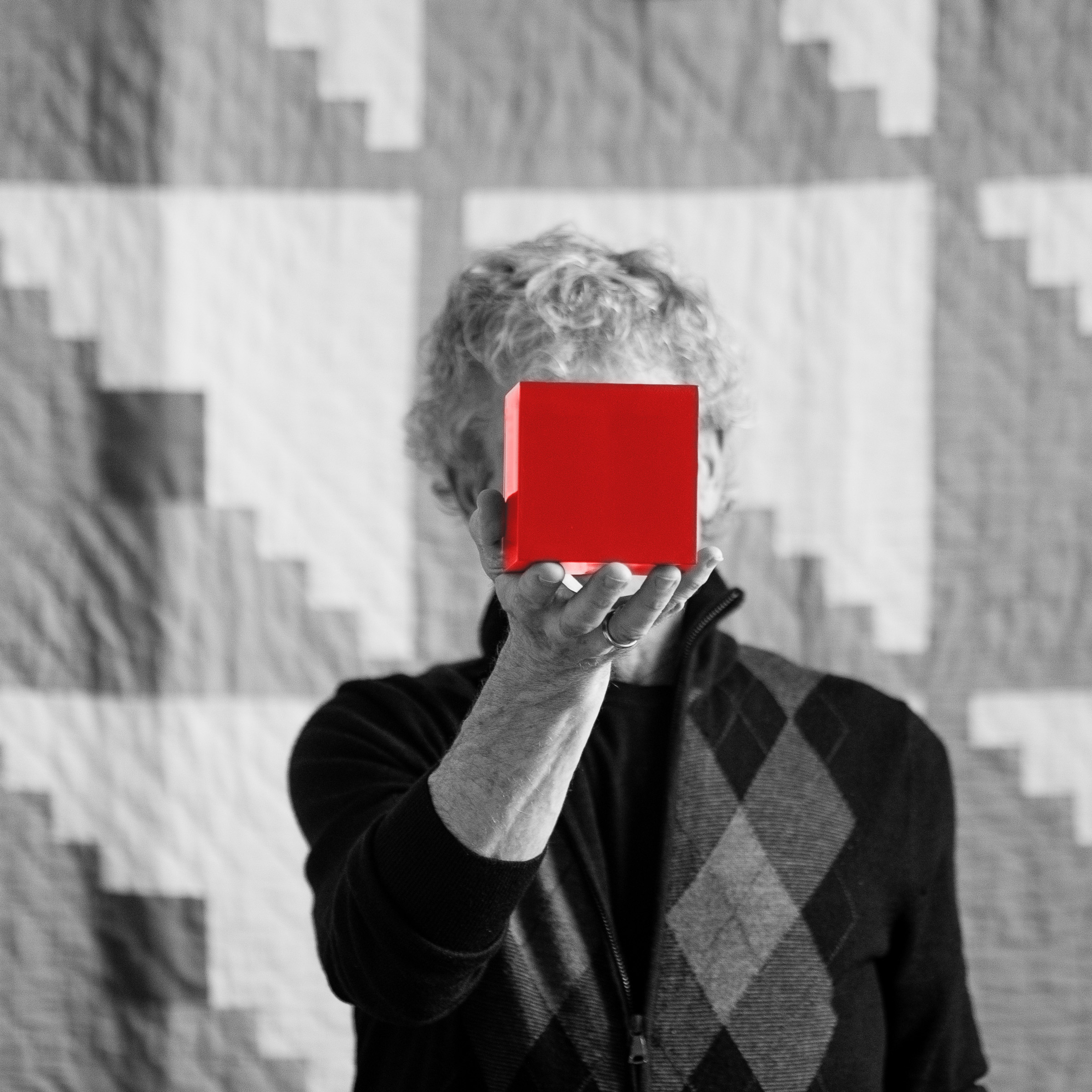 Roger Sametz in black and white, holding a red cube in front of his face