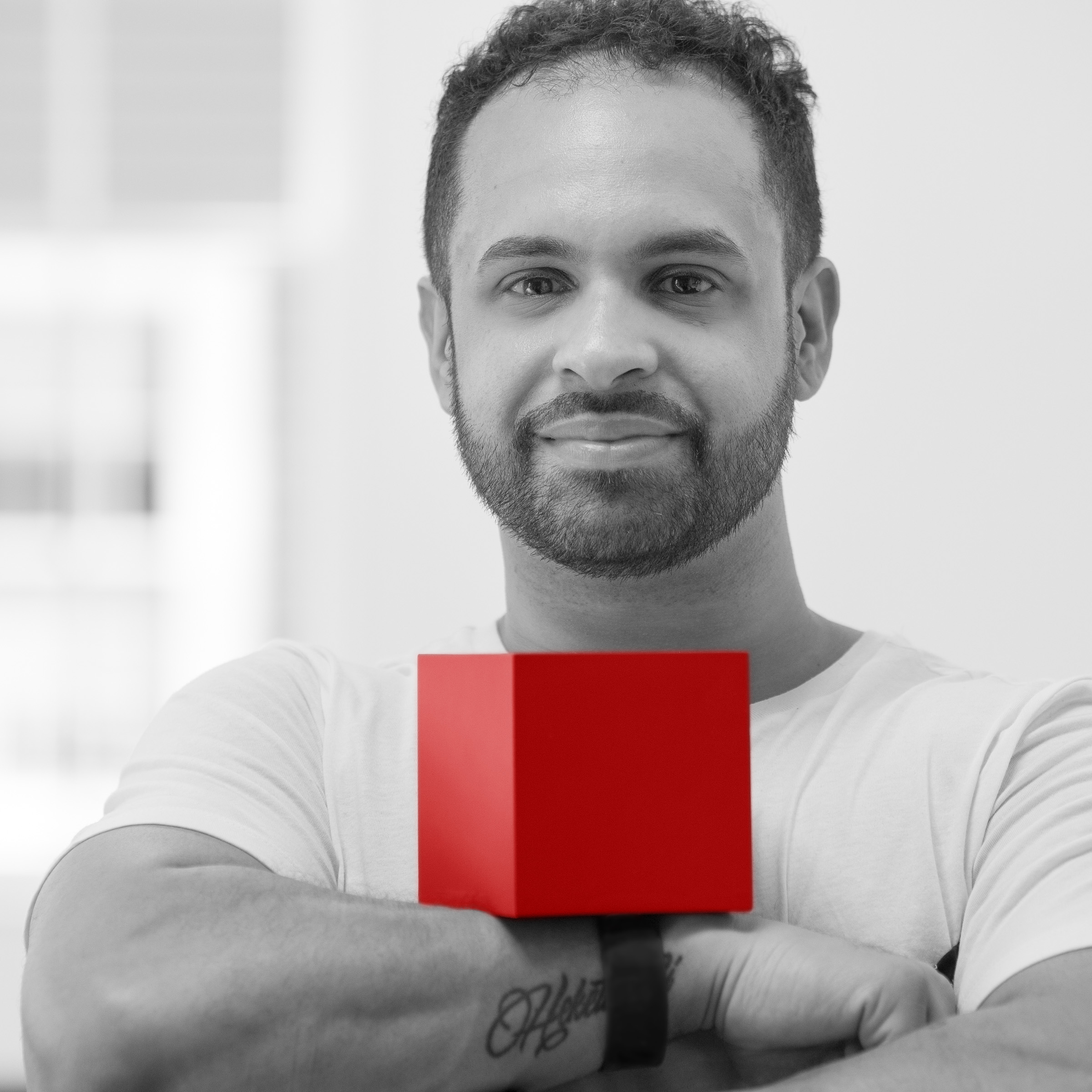 Joel Zayas in black and white with a bright red cube resting on his crossed arms