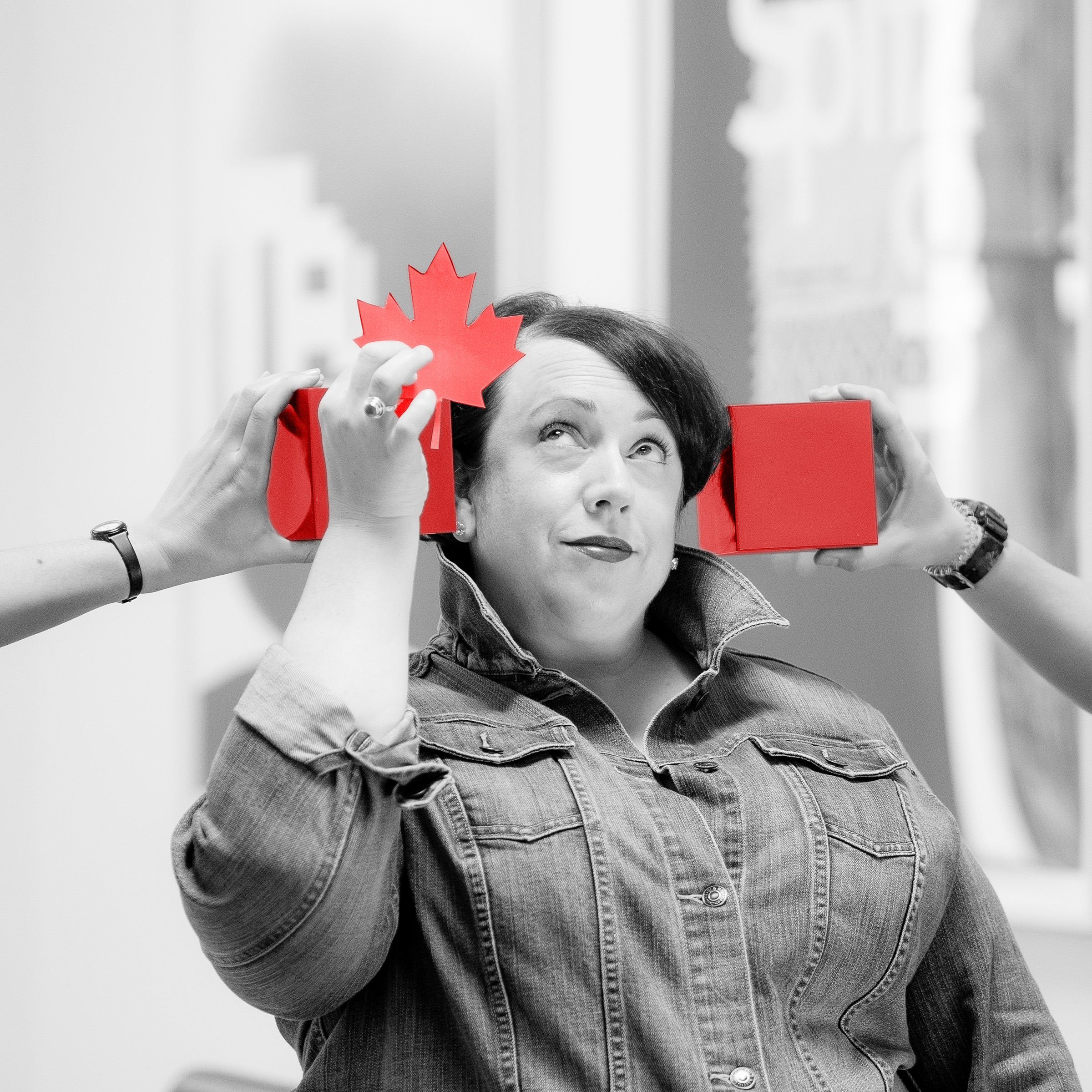 "Meg Fowler Tripp in black and white holding up a bright piece of paper in the shape of a Canadian maple leaf. Two hands are holding red cubes on either side of her head, creating a ""Canadian Flag"""