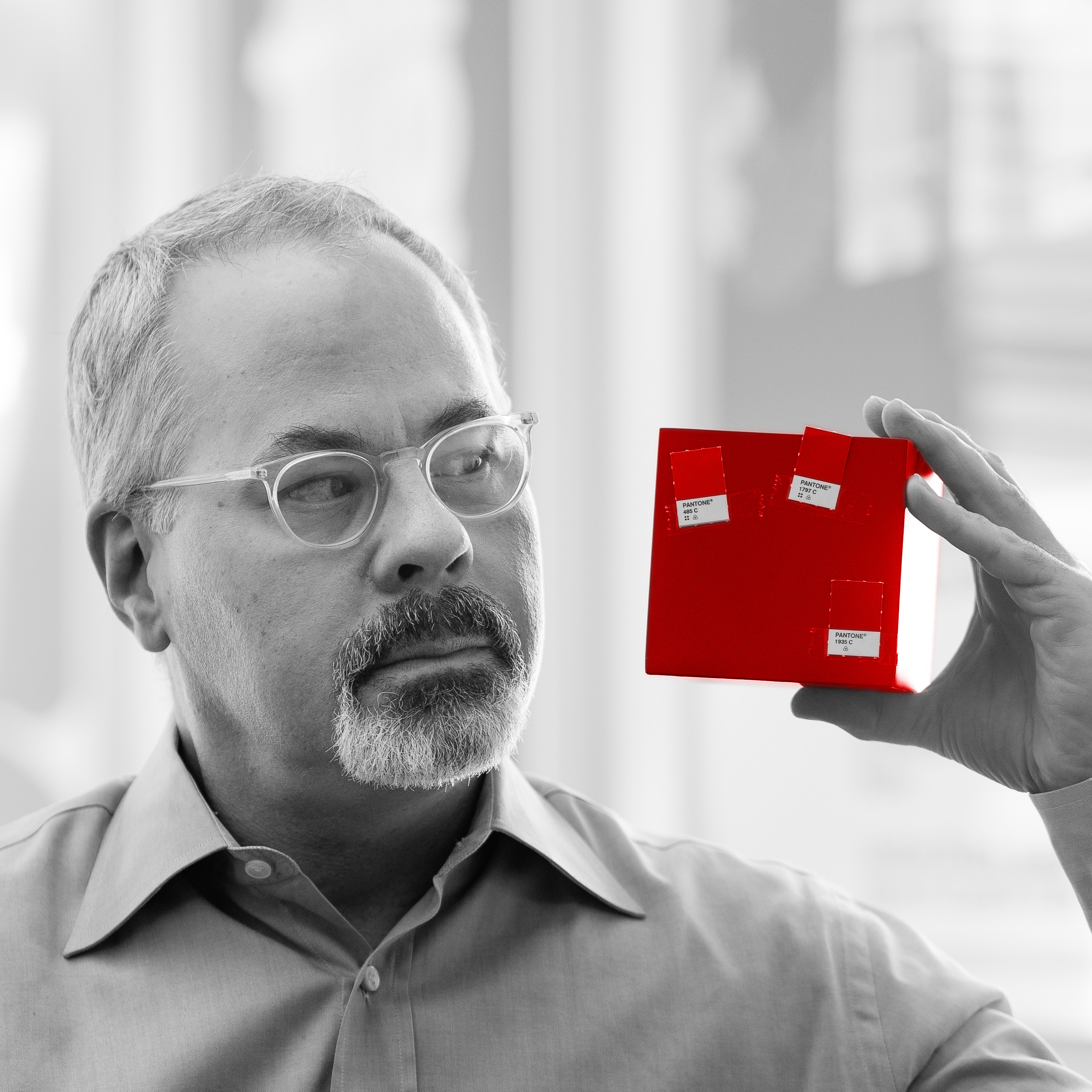 Michael Eads in black and white holding a bright red cube with Pantone swatches taped on to it